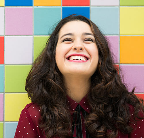 Woman smiling in front of colored tiles